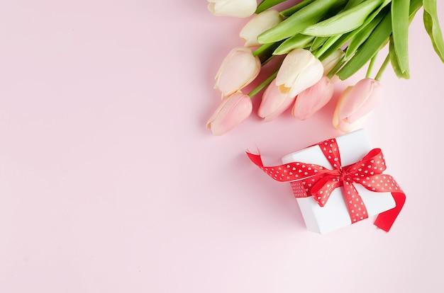 분홍색 배경에 튤립 부케와 선물 상자