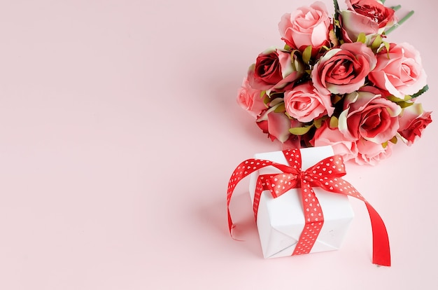 Gift box with bouquet of tred rose on pink background. spring or holiday concept