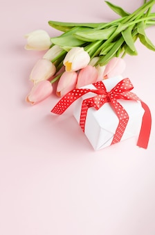 Gift box with bouquet of tulips on pastel pink table.