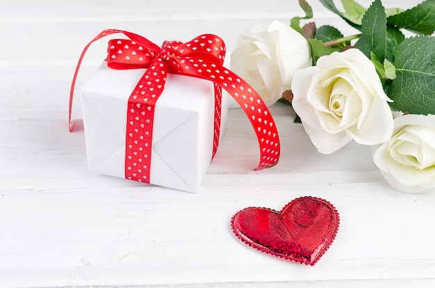 Gift box with bouquet of white rose on white wooden table.