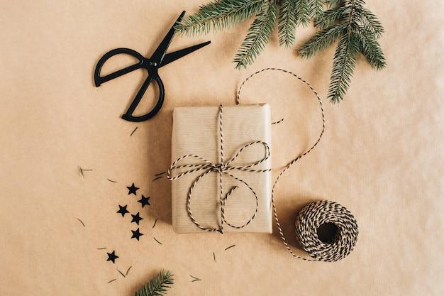 활과 공예 종이 표면에 전나무 바늘 장식 선물 상자. 크리스마스 최소한의 구성. flatlay, 평면도