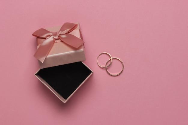 ピンクのパステルカラーの背景にリボンとゴールドのリングが付いたギフトボックス。結婚式のコンセプト。宝石。上面図。フラットレイ