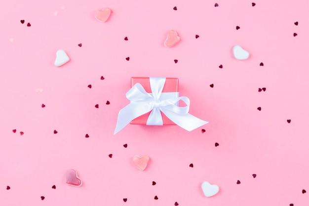 Подарочная коробка с бантом и конфетти сердца на светло-розовом фоне