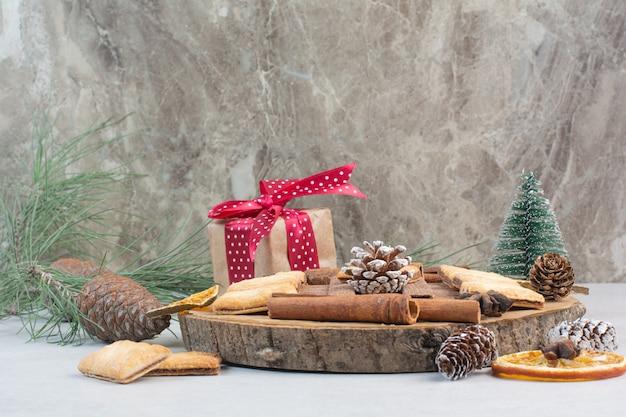 Подарочная коробка с бантом и шишками на деревянной тарелке. фото высокого качества