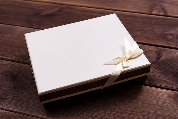 Gift box with bow for anniversary or christmas on a dark wooden table