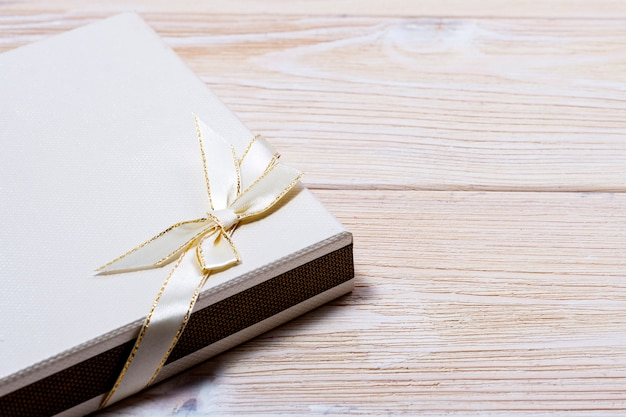 Gift box with bow for anniversary or christmas on a light wooden table