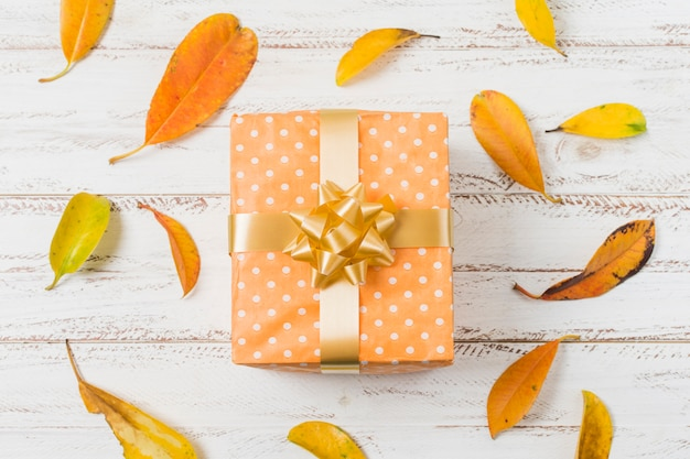 Gift box with bow and autumn leaves over wooden surface