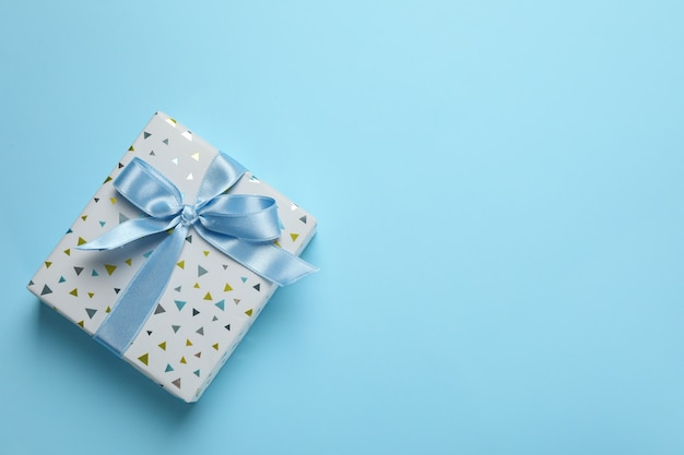 Gift box with bow on blue background, space for text