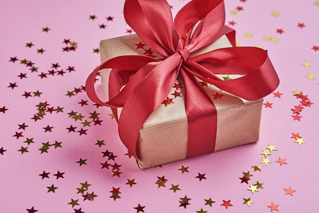 Gift box with bow and confetti, close up