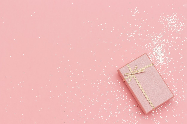 Gift box with bow in corner on pink pastel background in minimal style