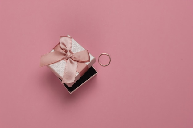 Gift box with bow and gold ring on pink pastel background. wedding concept. jewelry. top view. flat lay