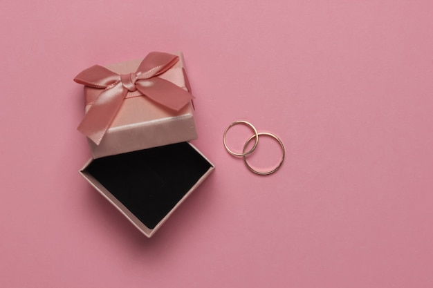 Gift box with bow and gold rings on pink pastel background. wedding concept. jewelry. top view. flat lay