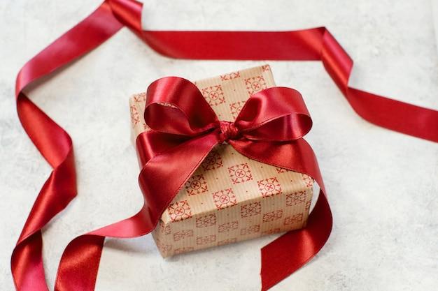 Подарочная коробка с бантом из красной атласной ленты на столе крупным планом
