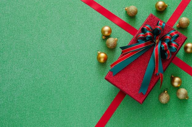 Подарочная коробка с бантовой лентой и рождественскими украшениями безделушек на зеленом.