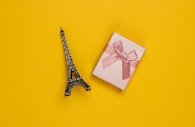 Подарочная коробка с бантом, статуэтка эйфелевой башни на желтом фоне. шоппинг в париже, сувениры