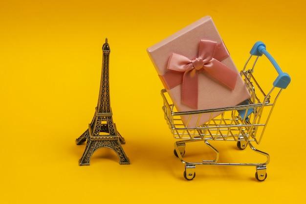Подарочная коробка с бантом, статуэтка эйфелевой башни, тележка для покупок на желтом фоне. шоппинг в париже, сувениры