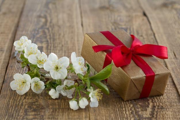 木製の背景に美しいジャスミンの花の枝が付いたギフトボックス。休日に贈り物をするという概念。