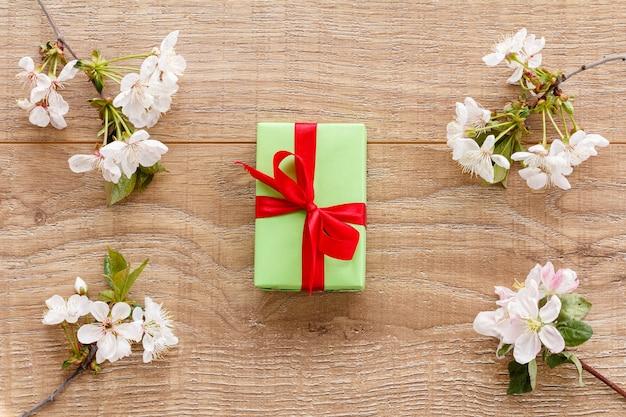 나무 배경에 꽃이 만발한 체리와 사과 나무 가지가 있는 선물 상자. 평면도. 휴일에 선물을 주는 개념.