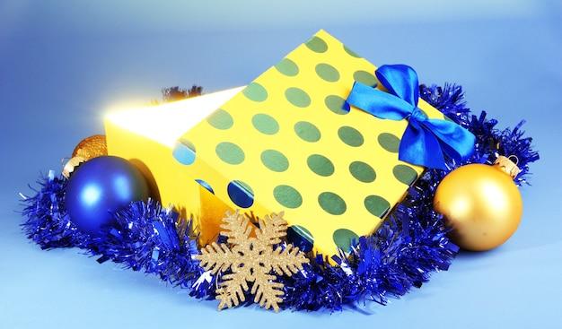 Подарочная коробка с ярким светом на синем фоне
