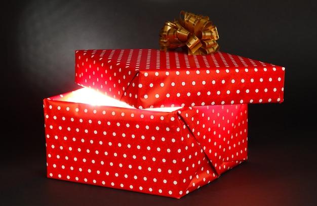Подарочная коробка с ярким светом на темно-сером фоне