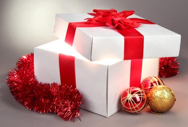Подарочная коробка с ярким светом на сером фоне