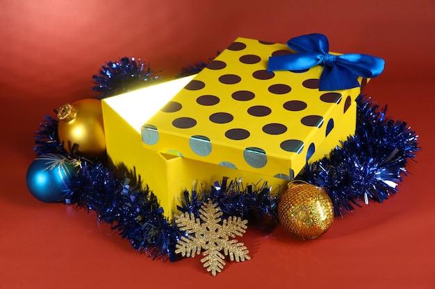 Подарочная коробка с ярким светом на красном фоне