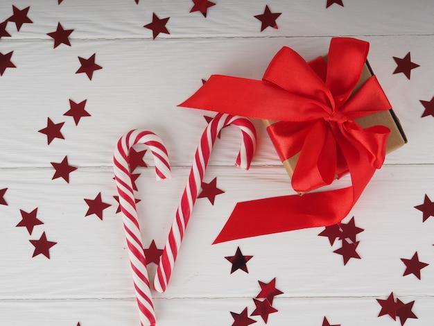Подарочная коробка с ярко-красной розовой лентой на белом фоне со звездами