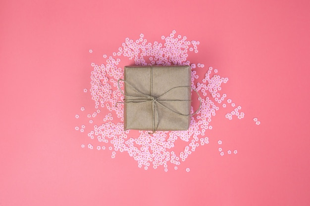 Gift box with brown kraft paper surrounded with pink daisies and flatlay pink background, spring