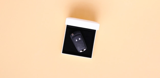 Gift box with car keys on beige background.flat lay, top view, copy space.concept car, car rental, gift, driving lessons, driving license. Premium Photo