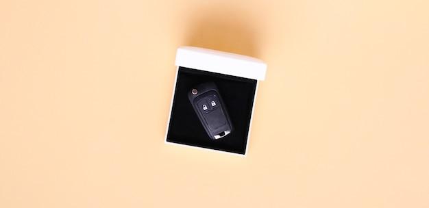 베이지 색 배경에 자동차 키와 선물 상자입니다. 평면 위치, 평면도, 복사 공간 개념 자동차, 자동차 렌탈, 선물, 운전 수업, 운전 면허증.