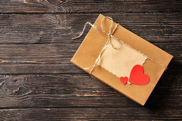 木の表面にカードと紙のハートが付いたギフトボックス