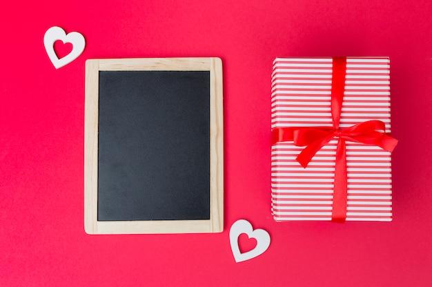 Подарочная коробка с классной доской и белыми сердечками на столе