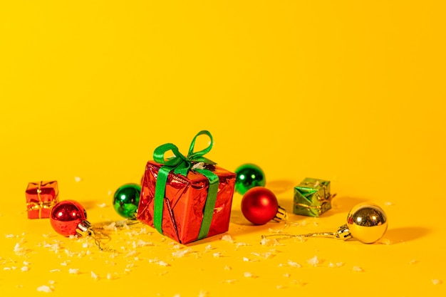 Gift box with a christmas present on a yellow background, among the new year's decorations.