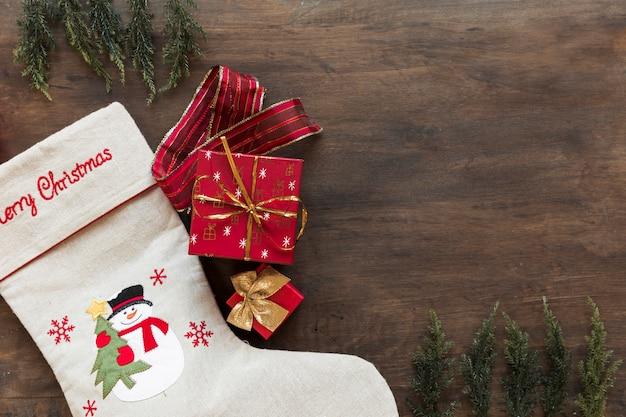 Gift box with christmas sock on table