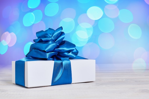 Gift box with a classic blue bow on a background with bokeh defocus background