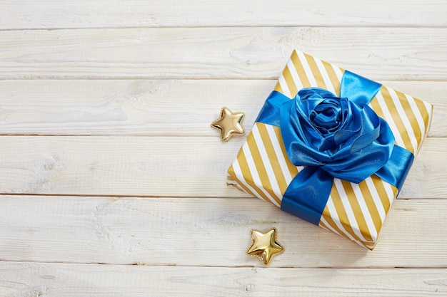Gift box with classic blue bows. striped wrapper, golden stars on a wooden wall. flatlay.