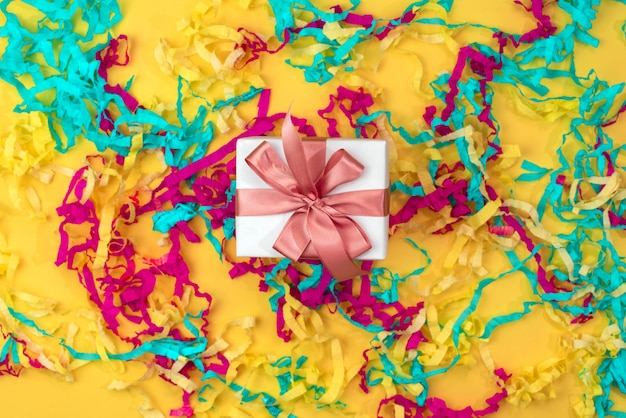 Gift box with colored streamers bright yellow background