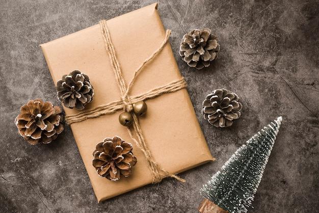 Confezione regalo con coni e piccoli abeti sul tavolo