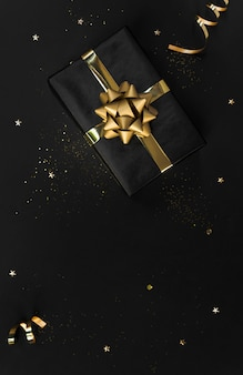 Gift box with decorations gold confetti on black  for christmas and  . copyspace