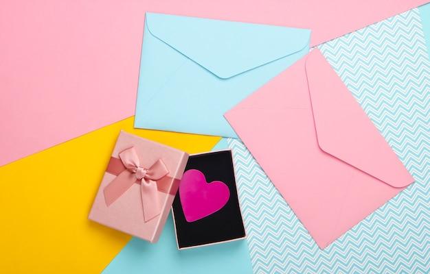 Подарочная коробка с декоративным сердцем и конвертами на цветном фоне. день святого валентина. тенденция пастельных тонов. вид сверху