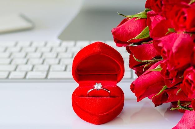 Подарочная коробка с бриллиантовым кольцом и красными розами на рабочем столе для концепции дня святого валентина.
