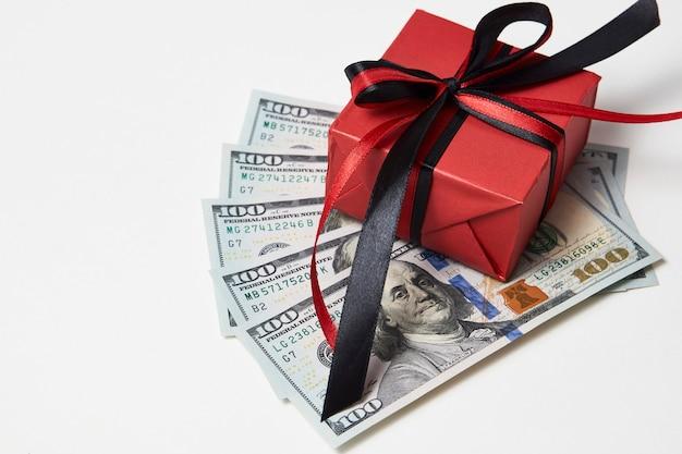 Подарочная коробка с долларовыми банкнотами на белом фоне. подарок в виде долларовых денег