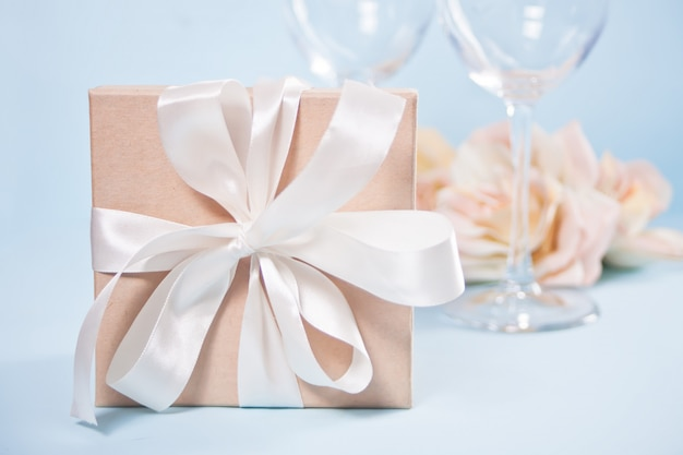 Gift box with empty two wineglasses and flowers on the background. romantic dinner concept.