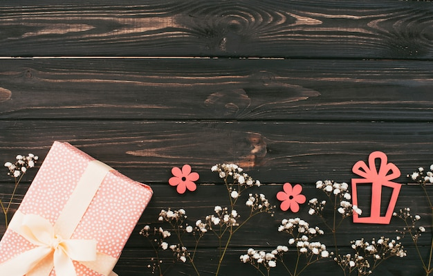 Gift box with flower branches on wooden table