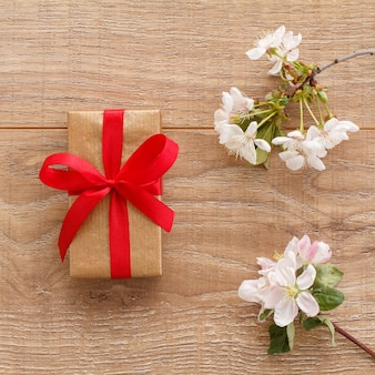Gift box with flowering branches of cherry and apple trees on the wooden surface
