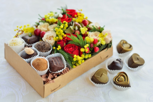Gift box with flowers and candies made of chocolate