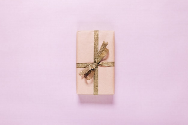 Gift in a box with a gold ribbon on a pink background