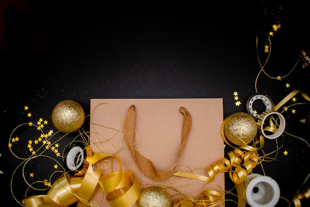 Gift box with golden bow on black background with decoration and sparkles