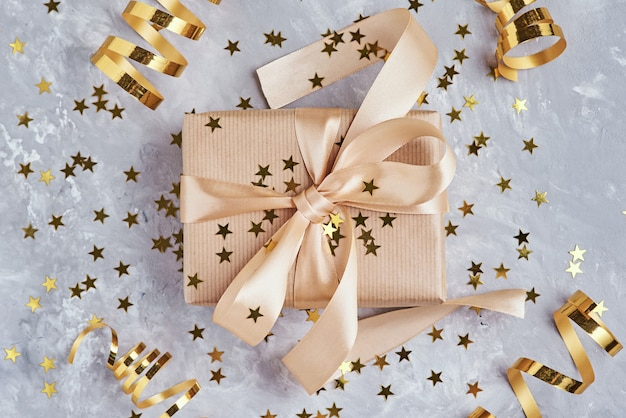 Gift box with golden bow and confetti, close up