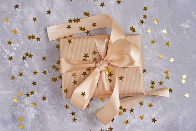Gift box with golden bow and confetti